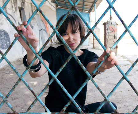 A girl behind the blue rusted bars photo