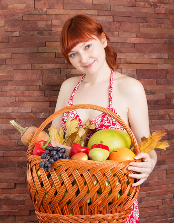 Redhead girl with a basket of autumn fruits and leaves photo