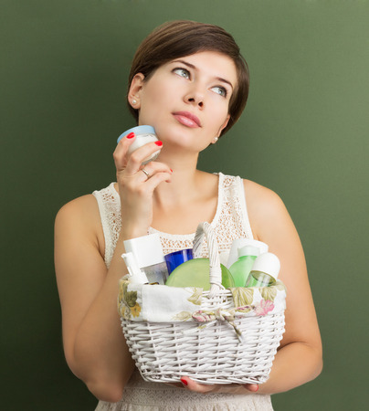 cosmetic products: Girl with a basket full of skin care products Stock Photo