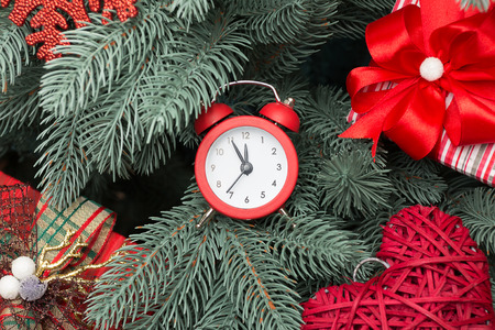 new year tree: Christmas present and red clock on a snowy background Stock Photo