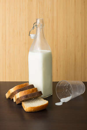 overthrown: Bottle of milk and bread on a wooden background Stock Photo