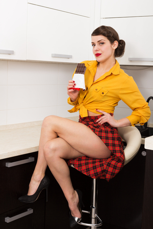 people sitting on chair: Stylish pin up girl with chocolate bar Stock Photo