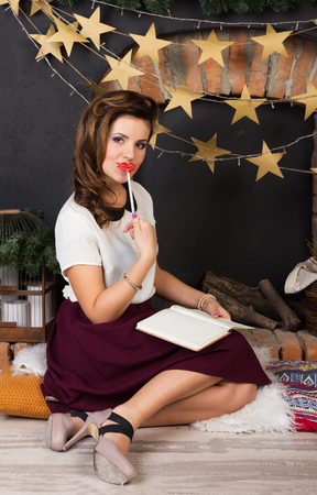 Beautiful girl with a diary near the fireplace photo
