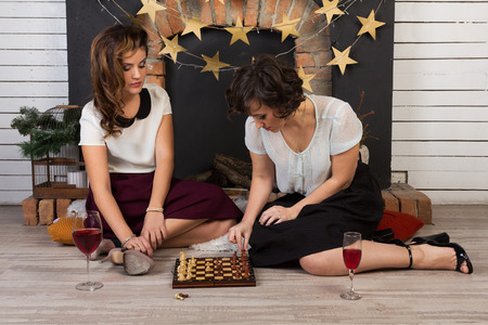 frienship: Two beautiful girl friends playing chess by the fireplace
