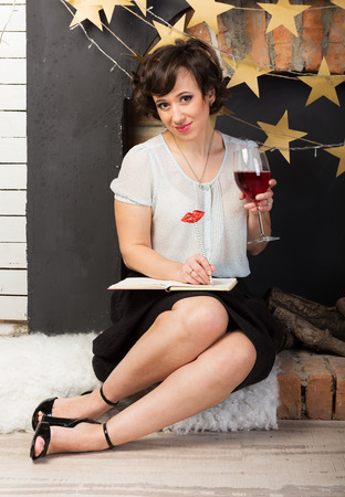 pencil skirt: Woman writing her journal with a glass of red wine Stock Photo