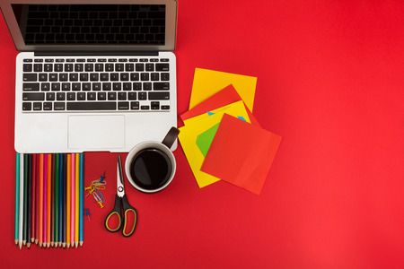 Creative messy workplace with laptop and stationery Stock Photo
