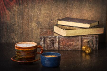 bibliophile: Coffee and a stack of old books. Retro look with added texture