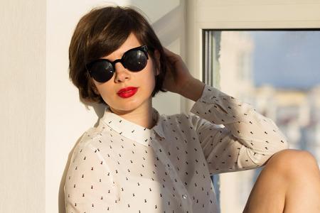 cabello rojo: Chica con gafas de so�ar despierto sentado junto a la ventana