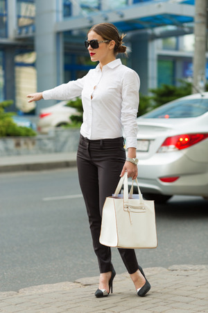 catching taxi: Stylish business woman in the big city Stock Photo