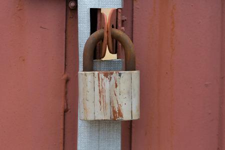 puertas de hierro: Candado viejo colgando de las puertas de hierro
