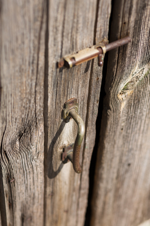 chipped paint: Old wooden door with chipped paint and rusted handle