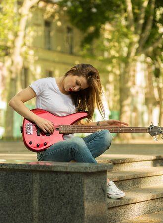 chica pensando: Muchacha con una guitarra en la ciudad. Imagen en tonos retro Foto de archivo