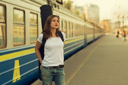 bass guitar women: Girl with a guitar at train station. Retro toned image