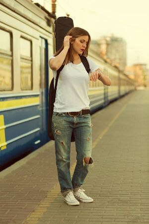 toned image: Girl with a guitar at train station. Retro toned image