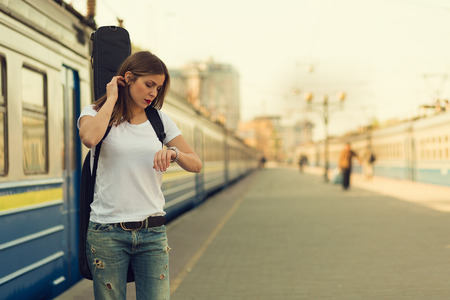women jeans: Girl with a guitar at train station. Retro toned image