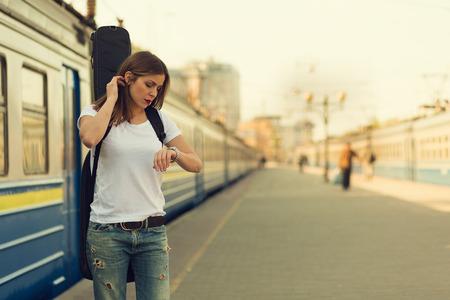 tren: Muchacha con una guitarra en la estaci�n de tren. Imagen en tonos retro Foto de archivo