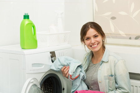 laundry detergent: Beautiful young girl doing laundry at home