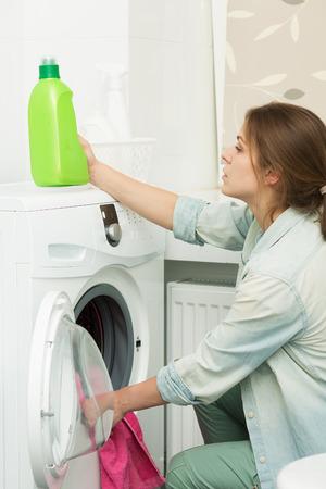 lavanderia: Hermosa joven lavando la ropa en casa