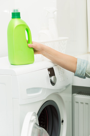 Bottle of detergent standing on a washing machine