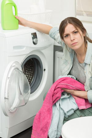 frowned: Beautiful young girl doing laundry at home