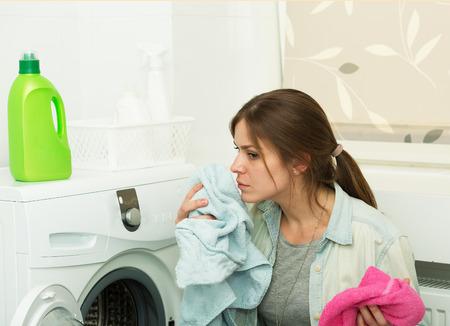 clothes washing: Hermosa joven lavando la ropa en casa