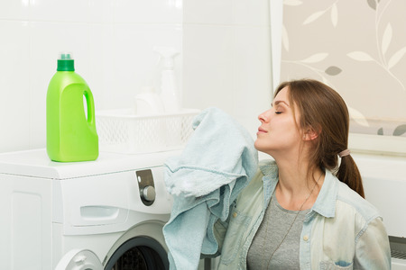 detergent: Beautiful young girl doing laundry at home