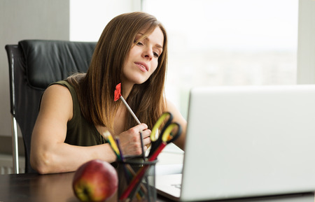 Beautiful woman working at the laptop in the office Stock Photo