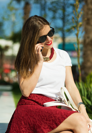 sidewalk talk: Beautiful young girl talking over the phone in the big city Stock Photo