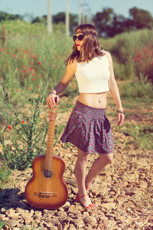 Beautiful hippie girl alone on the countryside road Stock Photo