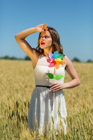 sunstroke: Happy girl with a colorful windmill in the field