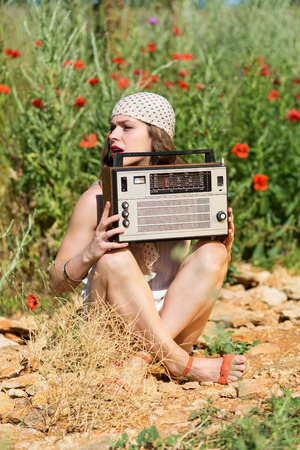 stylish girl: Beautiful stylish girl with an old stereo in the summer field