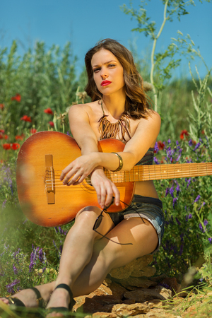 stylish girl: Beautiful stylish girl with a guitar in the summer field