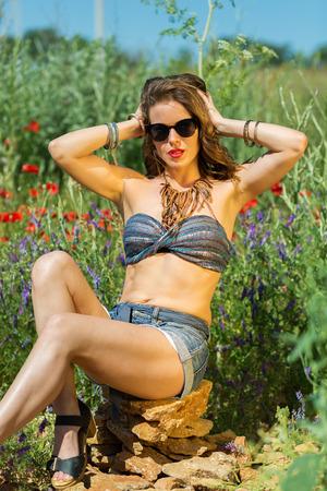 sexy beine: Schönes stilvolles Mädchen auf dem Sommergebiet