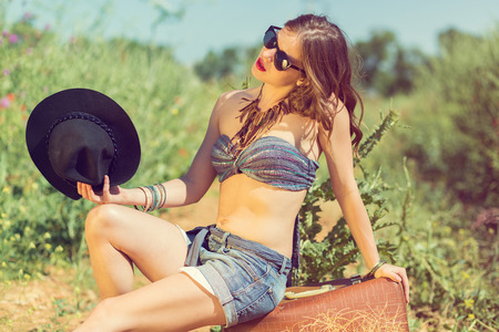 Beautiful girl with a suitcase in the summer field. Retro toned image Stock Photo