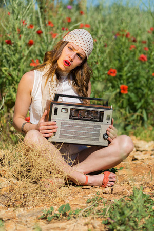 Beautiful stylish girl with an old stereo in the summer field