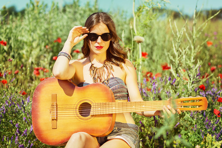 Beautiful stylish girl with a guitar in the summer field