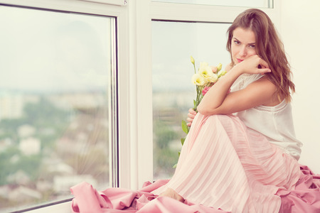 Romantic girl in long gown sitting by the window
