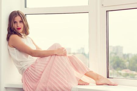 falda: Muchacha romántica en vestido largo sentado junto a la ventana Foto de archivo