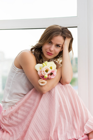 Romantic girl with flowers sitting by the window Stock Photo