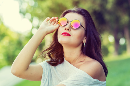 naughty girl: Beautiful girl in round sunglasses walking in the park Stock Photo