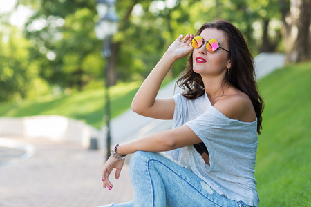 woman looking up: Beautiful girl in round sunglasses walking in the park Stock Photo