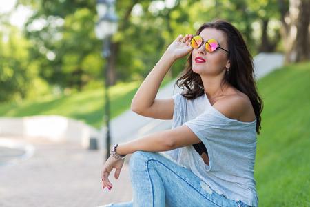 personas mirando: Muchacha hermosa en gafas de sol redondas caminando en el parque