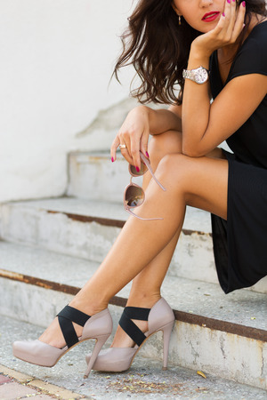 looking at watch: Stylish young woman standing by the stairs