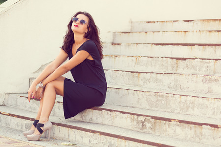 sit: Stylish young woman standing by the stairs