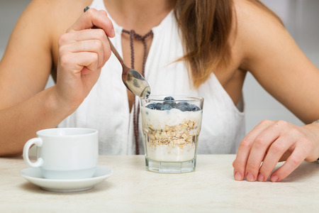 Beautiful woman having coffee, fruits and oatmeal for breakfast Stock Photo