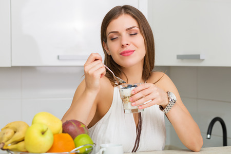 eating breakfast: Beautiful woman having coffee, fruits and oatmeal for breakfast Stock Photo