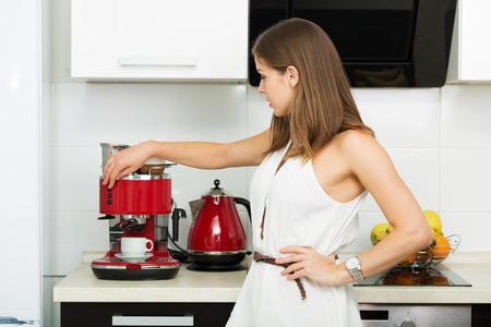 Beautiful woman making coffee for breakfast in the kitchen Stock Photo
