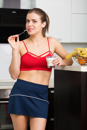 table skirt: Beautiful woman having oatmeal with berries for breakfast Stock Photo
