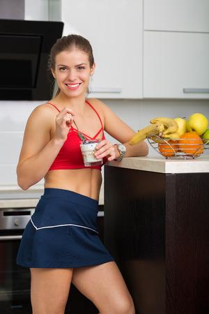 table skirt: Beautiful woman having an oatmeal for breakfast Stock Photo