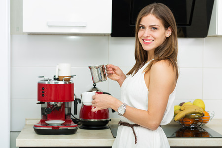 making coffee: Beautiful woman making coffee for breakfast in the kitchen Stock Photo